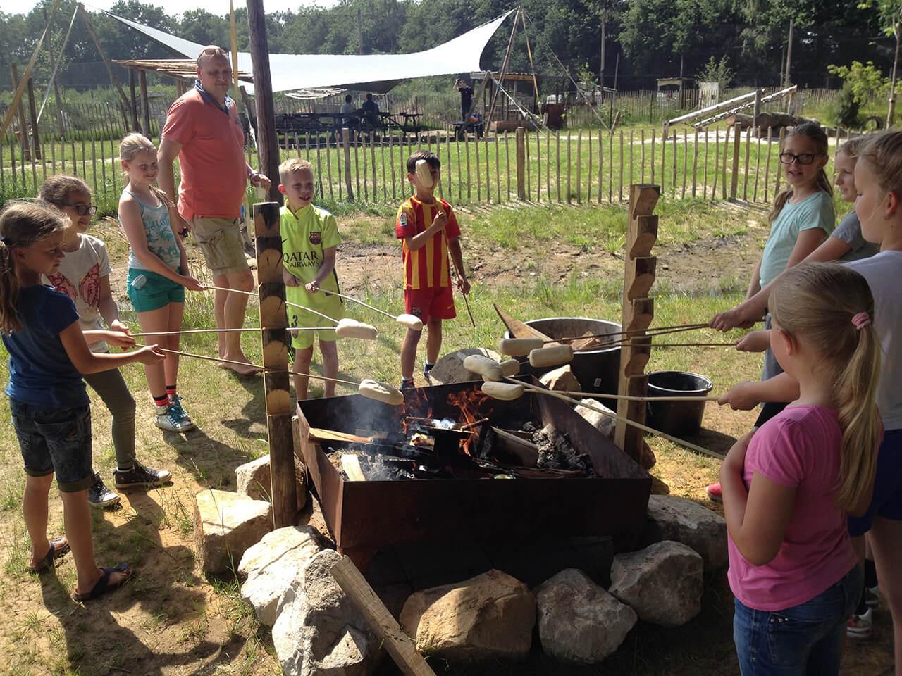 Kinderen bakken een lekker broodje boven kampvuur