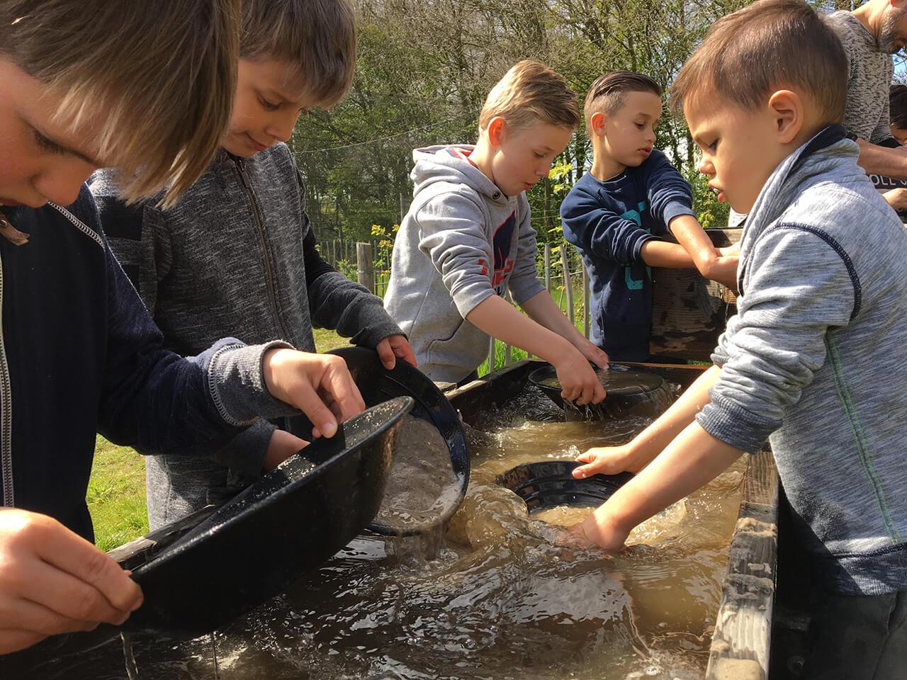 kinderen wassen vol aandacht hun goudpan uit